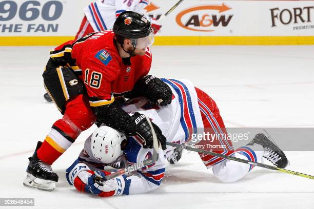 Matt Stajan of the Calgary Flames knocks down Peter Holland of the New York Rangers during an NHL game on March 2 2018 at the Scotiabank Saddledome...
