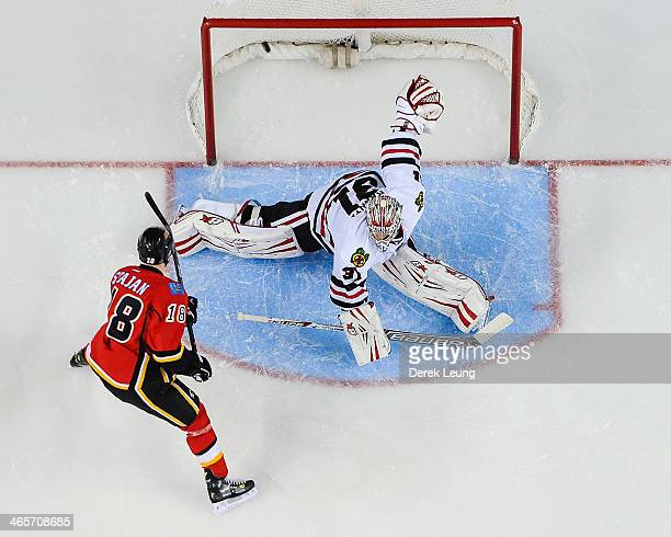 Matt Stajan of the Calgary Flames scores on Antti Raanta of the Chicago Blackhawks during an NHL game at Scotiabank Saddledome on January 28 2014 in...