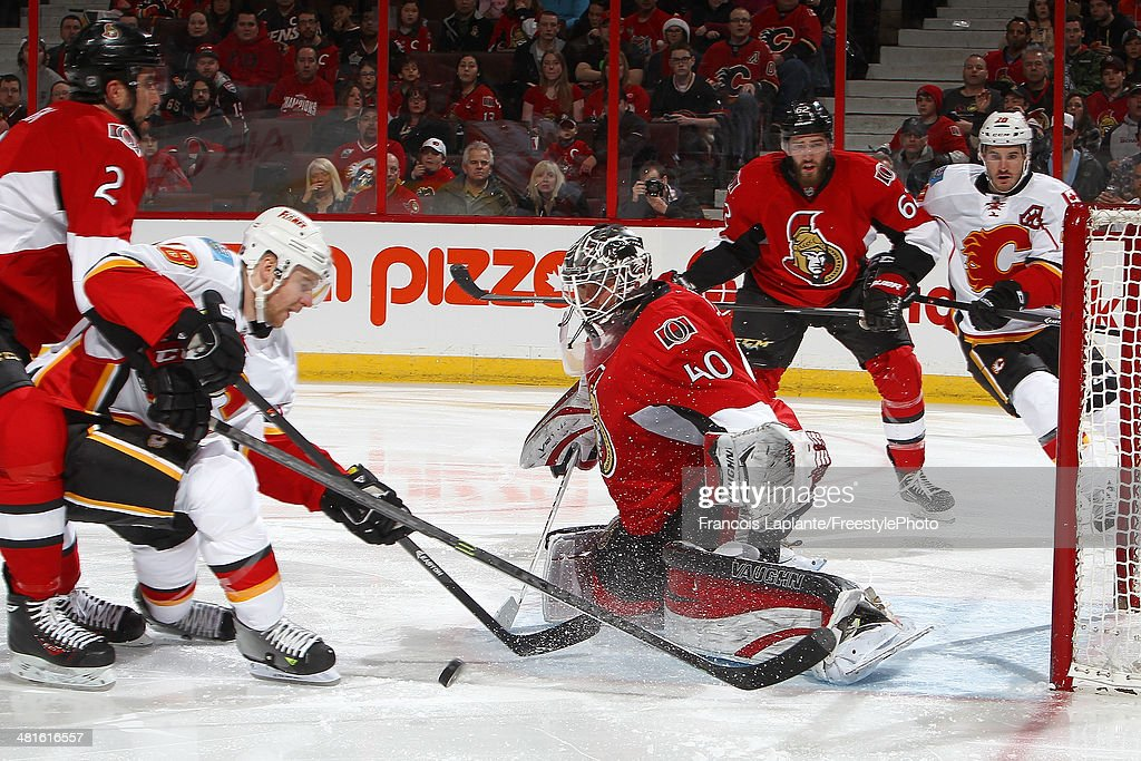 Matt Stajan #18 of the Calgary Flames shoots the puck against Robin Lehner #40 of the Ottawa Senators as Jared Cowen #2 defends during an NHL game at Canadian Tire Centre on March 30, 2014 in Ottawa, Ontario, Canada.