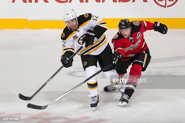 Matt Stajan of the Calgary Flames skates against Jarome Iginla of the Boston Bruins at Scotiabank Saddledome on December 10 2013 in CalgaryAlberta...
