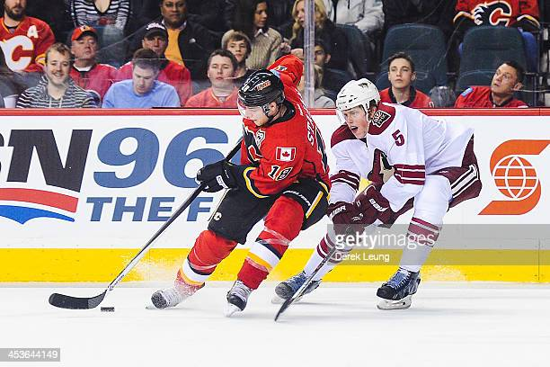 Matt Stajan of the Calgary Flames skates with the puck past Connor Murphy of the Phoenix Coyotes during an NHL game at Scotiabank Saddledome on...