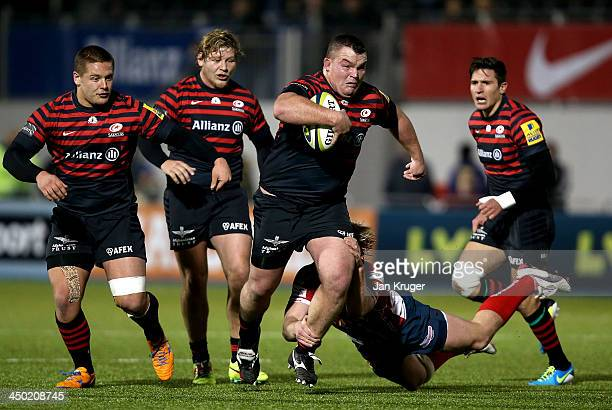 Matt Stevens of Saracens crashes through the tackle of Dan Thomas of Scarlets during the LV= Cup match between Saracens and Scarlets at Allianz Park...
