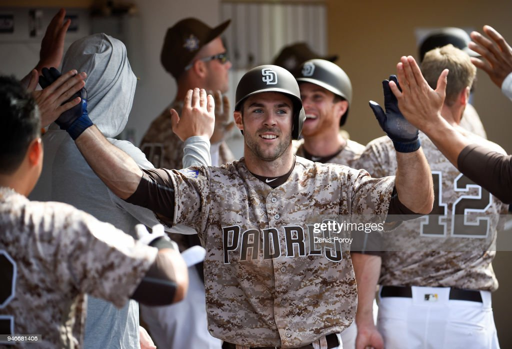 Matt Szczur #23 of the San Diego Padres, foreground, and Cory Spangenberg #15 are congratulated after scoring during the seventh inning of a baseball game against the San Francisco Giants at PETCO Park on April 15, 2018 in San Diego, California. All players are wearing #42 in honor of Jackie Robinson Day.