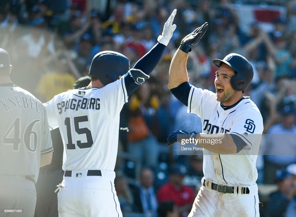 Matt Szczur #23 of the San Diego Padres is congratulated by Cory Spangenberg #15 after scoring during the ninth inning on Opening Day against the Milwaukee Brewers at PETCO Park on March 29, 2018 in San Diego, California.