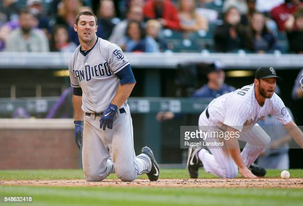 Matt Szczur of the San Diego Padres slides safely at home on a sacrifice bunt as Greg Holland of the Colorado Rockies can't hold onto the ball of a...