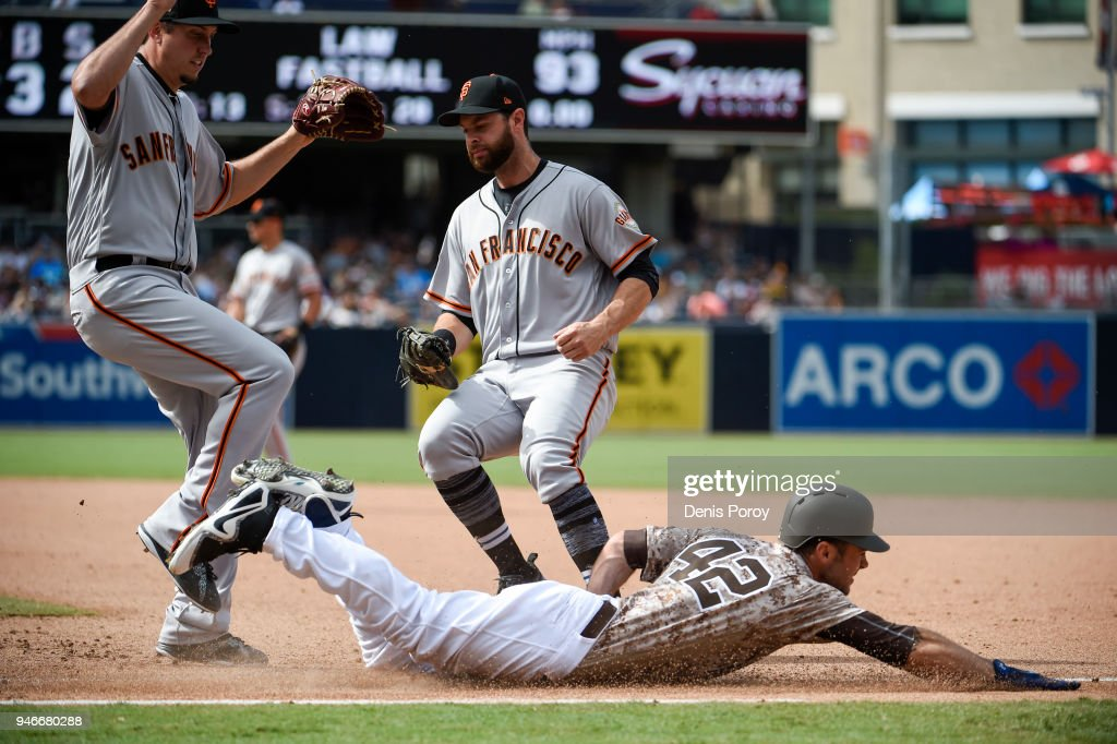 Matt Szczur #23 of the San Diego Padres slides safely into first base as Derek Law #64 of the San Francisco Giants, (L) and Brandon Belt #9 look on during the seventh inning of a baseball game at PETCO Park on April 15, 2018 in San Diego, California. All players are wearing #42 in honor of Jackie Robinson Day.