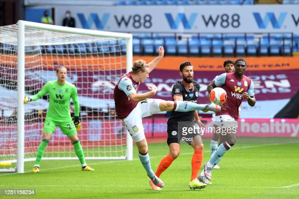 Matt Targett of Aston Villa clears the ball from Olivier Giroud of Chelsea during the Premier League match between Aston Villa and Chelsea FC at...