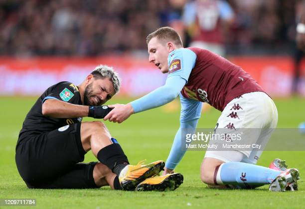 Matt Targett of Aston Villa consoles Sergio Aguero of Manchester City as he reacts with an injury that forces him to be substituted during the...