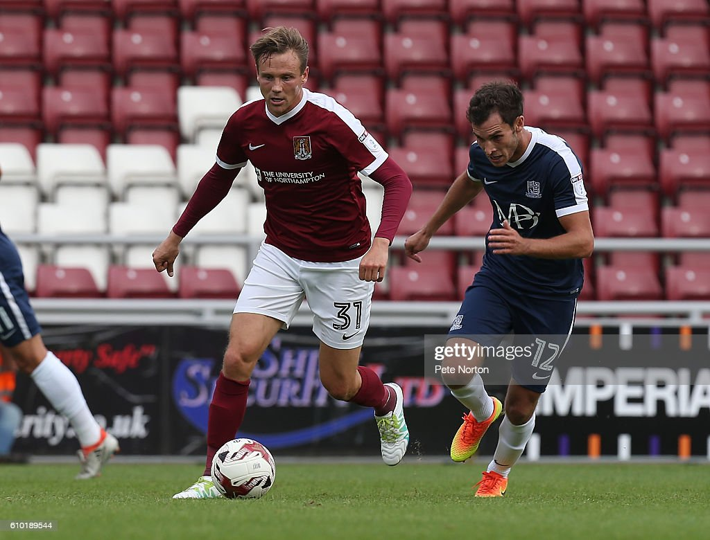 Matt Taylor of Northampotn Town moves forward with the ball away from Will Atkinson of Southend United during the Sky Bet League One match between Northampton Town and Southend United at Sixfields on September 24, 2016 in Northampton, England.