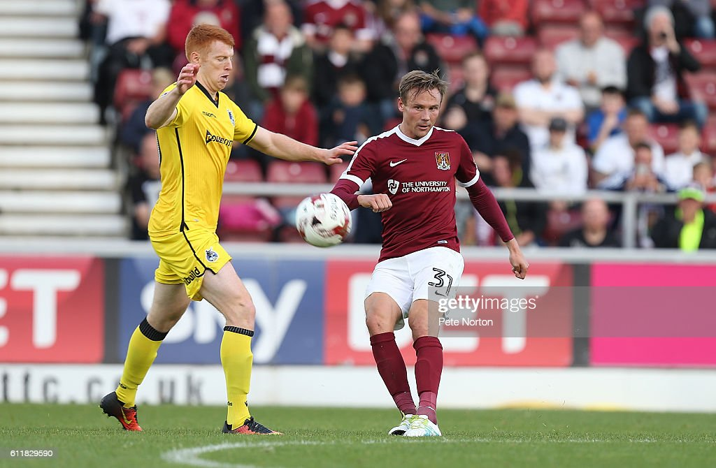 Matt Taylor of Northampton Town plays the ball past Rory Gaffney of Bristol Rovers during the Sky Bet League One match between Northampton Town and Bristol Rovers at Sixfields Stadium on October 1, 2016 in Northampton, England.