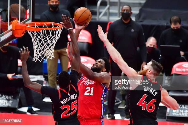 Matt Thomas of the Toronto Raptors shoots against Chris Boucher and Aron Baynes of the Toronto Raptors during the second half at Amalie Arena on...