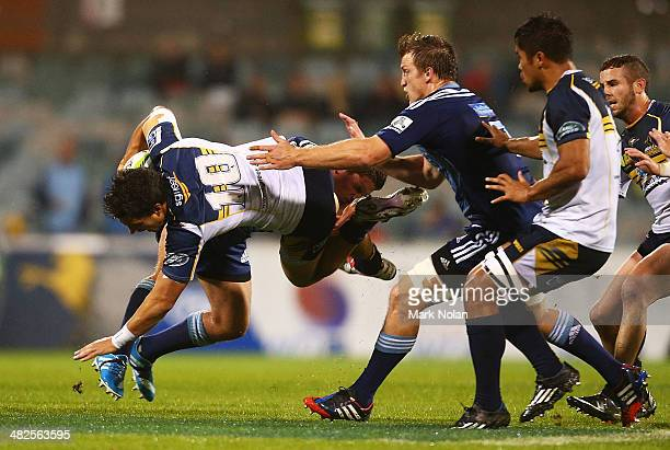Matt Toomua of the Brumbies is tackled during the round eight Super Rugby match between the Brumbies and the Bulls at Canberra Stadium on April 4,...
