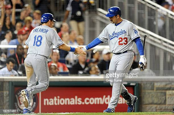 Matt Treanor of the Los Angeles Dodgers celebrates with Adrian Gonzalez after scoring in the fourth inning against the Washington Nationals at...