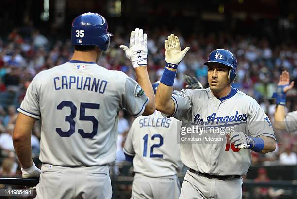 Matt Treanor of the Los Angeles Dodgers highfives Chris Capuano after hitting a tworun home run against the Arizona Diamondbacks during the second...