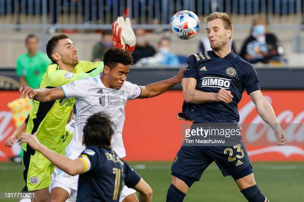 Matt Turner and Brandon Bye of the New England Revolution defend a header by Kacper Przybylko of the Philadelphia Union during the first half and at...