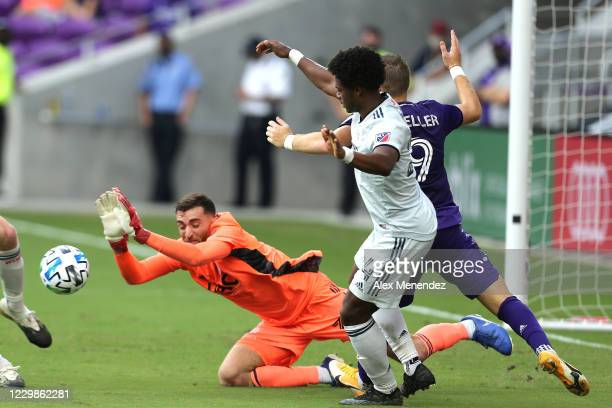 Matt Turner of New England Revolution makes a save against Chris Mueller of Orlando City SC as DeJuan Jones of New England Revolution helps defend...