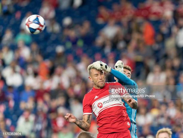 Matt Turner of New England Revolution punches ball away from Francisco Calvo of Chicago Fire during a game between Chicago Fire and New England...