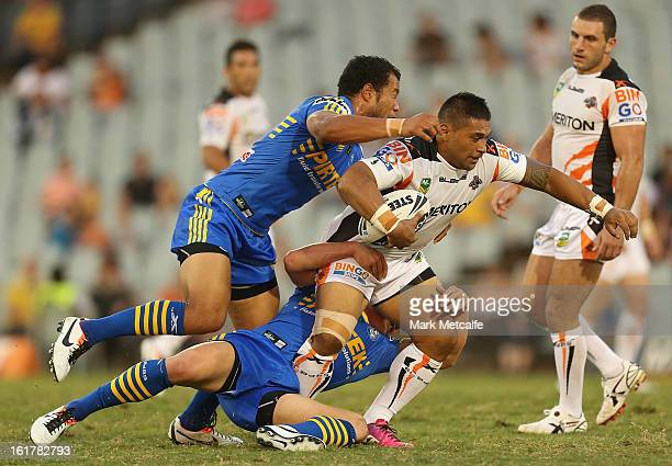 Matt Utai of the Tigers is tackled during the NRL trial match between the Wests Tigers and the Parramatta Eels at Campbelltown Sports Stadium on...