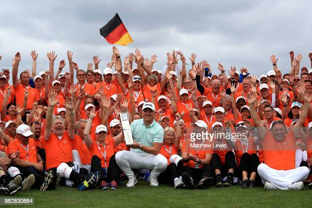 Matt Wallace of England celebrates with the trophy and tournament volunteers after winning the BMW International Open at Golf Club Gut Larchenhof on...