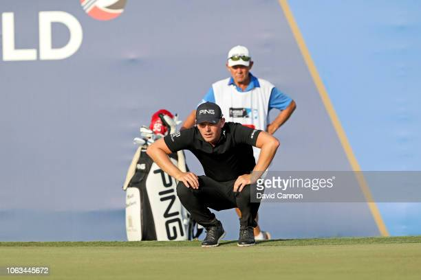 Matt Wallace of England lines up his third shot on the par 5 18th hole with his caddie Dave McNeilly during the final round of the DP World Tour...