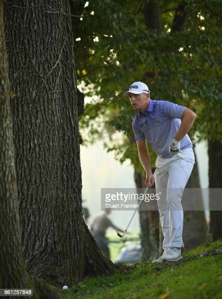 Matt Wallace of England looks to play a shot by a tree on the 18th hole during the third round of the Italian Open at Golf Club Milano Parco Reale di...