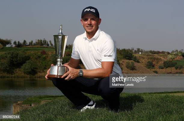 Matt Wallace of England poses for a picture with the trophy after winning the play off during day four of The Hero Indian Open at Dlf Golf and...