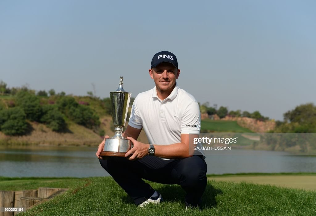 Matt Wallace of England poses with a trophy after winning the Hero Indian Open 2018 golf tournament at DLF Golf and Country Club in Gurugram on the outskirts of New Delhi on March 11, 2018. /