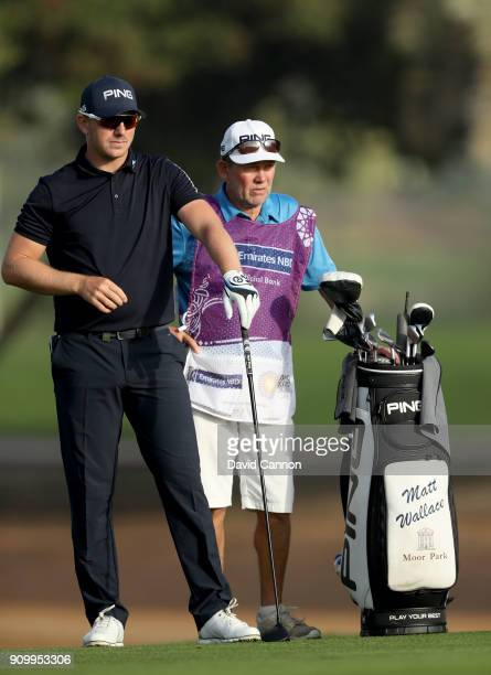 Matt Wallace of England waits to play his second shot on the par 5 third hole with his caddie Dave McNealy during the first round of the Omega Dubai...