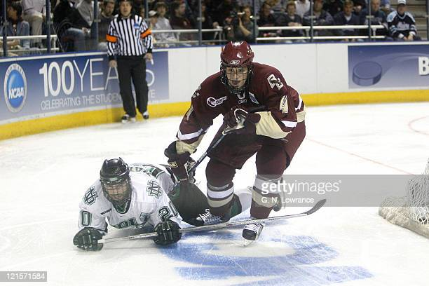 Matt Watkins of North Dakota takes a fall as Mike Brennan of Boston College skates around in the semifinals of the NCAA frozen four at the Bradley...