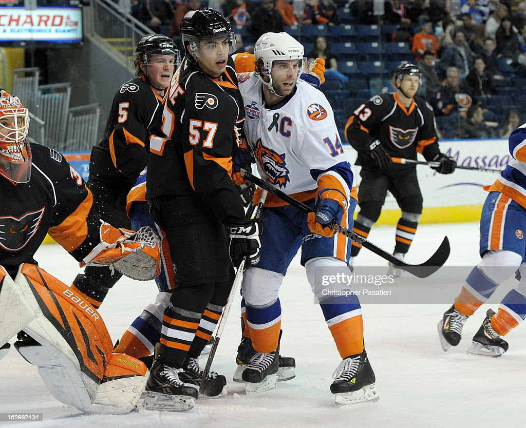 Matt Watkins #14 of the Bridgeport Sound Tigers and Matt Mangene #57 of the Adirondack Phantoms battle for position during an American Hockey League game on March 2, 2013 at the Webster Bank Arena at Harbor Yard in Bridgeport, Connecticut.