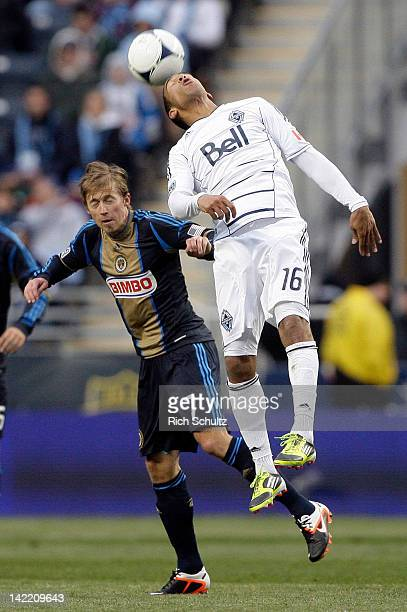 Matt Watson of the Vancouver Whitecaps heads the ball in front of Brian Carroll of the Philadelphia Union during the second half of a Major League...