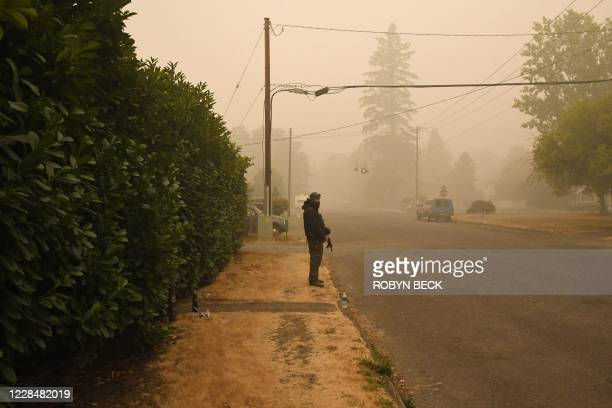 Matt Watts stands guard with firearms outside his home after wildfires and heavy smoke caused many of his neighbors to evacuate the area in Estacada...