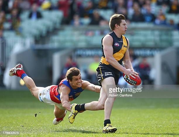 Matt White of the Tigers avoids a challenge from Jed Adcock of the Lions during the round 20 AFL match between the Richmond Tigers and the Brisbane...