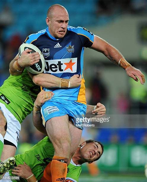 Matt White of the Titans is tackled during the round 24 NRL match between the Gold Coast Titans and the Canberra Raiders at Skilled Park on August 20...