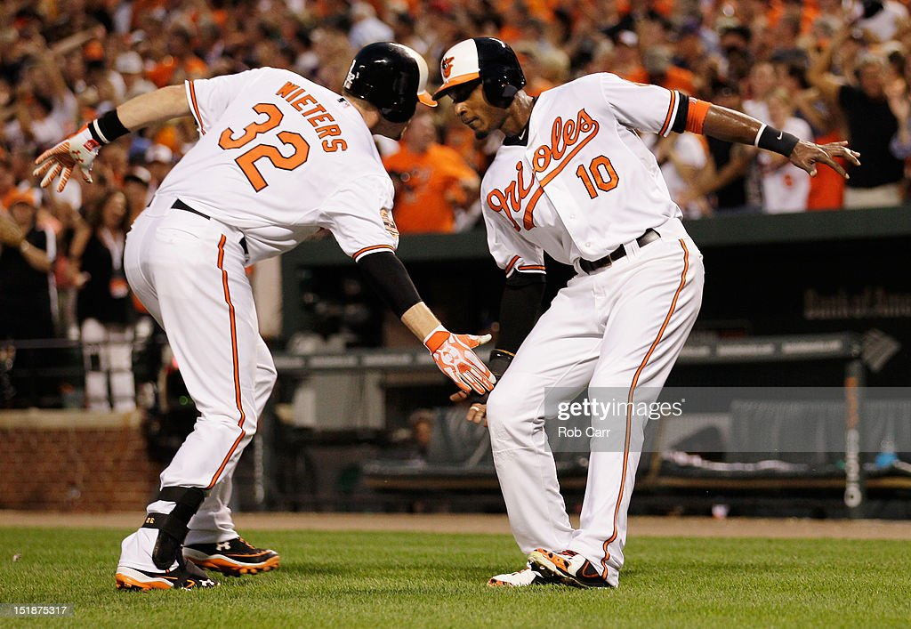 Matt Wieters #32 and Adam Jones #10 of the Baltimore Orioles celebrate after Wieters hit a home run against the New York Yankees at Oriole Park at Camden Yards on September 6, 2012 in Baltimore, Maryland.