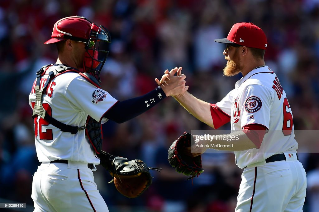 Matt Wieters #32 and Sean Doolittle #62 of the Washington Nationals celebrate after the Nationals defeated the Colorado Rockies 6-2 at Nationals Park on April 14, 2018 in Washington, DC.