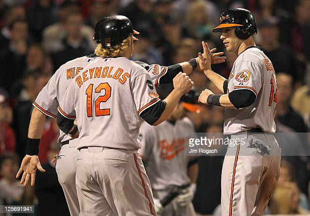 Matt Wieters Mark Reynolds and Nolan Reimold of the Baltimore Orioles celebrate scoring in the eighth against the Boston Red Sox at Fenway Park...