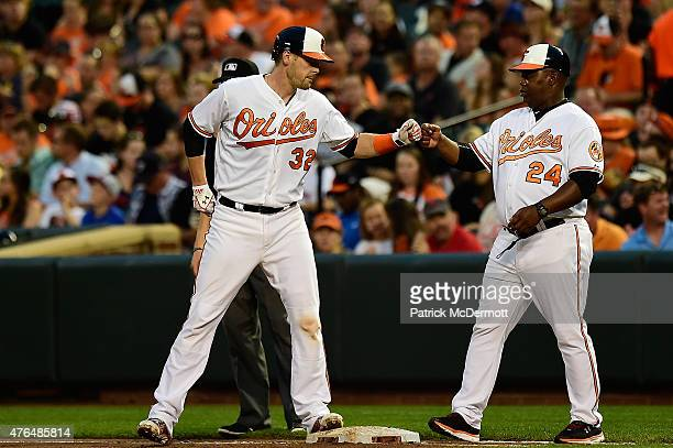 Matt Wieters of the Baltimore Orioles celebrates with first base coach Wayne Kirby after hitting a single in the fourth inning during a baseball game...