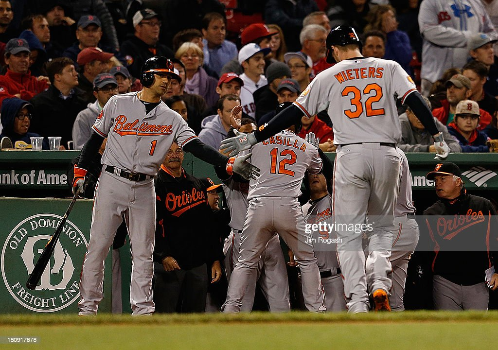 Matt Wieters #32 of the Baltimore Orioles celebrates with teammates after he knocked in the winning run with a sacrifice fly on a pitch from Koji Uehara #19 of the Boston Red Sox in the 9th inning at Fenway Park on September 17 in Boston, Massachusetts.