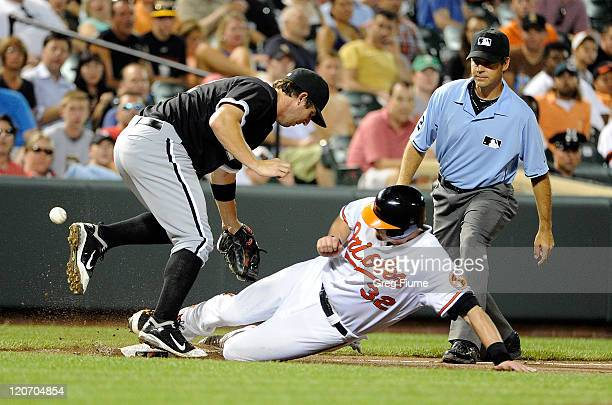 Matt Wieters of the Baltimore Orioles slides safely into third base knocking the ball away from Brent Morel of the Chicago White Sox at Oriole Park...