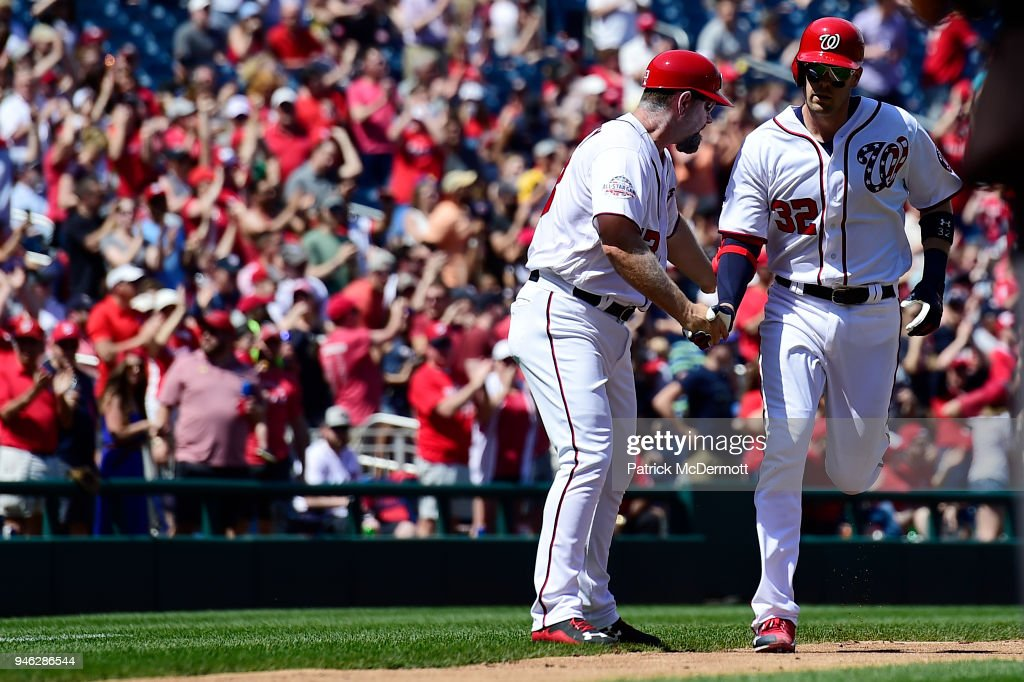 Matt Wieters #32 of the Washington Nationals celebrates with third base coach Bob Henley #13 as he rounds third base after hitting a solo home run in the fourth inning against the Colorado Rockies at Nationals Park on April 14, 2018 in Washington, DC.