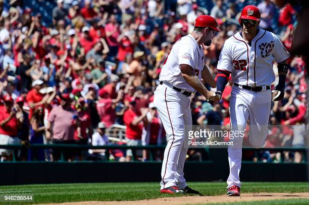 Matt Wieters of the Washington Nationals celebrates with third base coach Bob Henley as he rounds third base after hitting a solo home run in the...