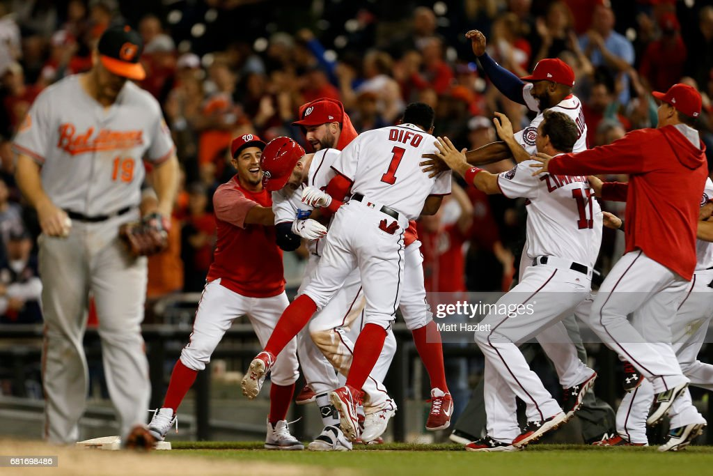 Matt Wieters #32 of the Washington Nationals is swarmed by his teammates after hitting a single two run RBI walk-off during the ninth inning to defeat the Baltimore Orioles 7-6 at Nationals Park on May 10, 2017 in Washington, DC.