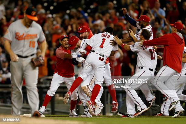 Matt Wieters of the Washington Nationals is swarmed by his teammates after hitting a single two run RBI walk-off during the ninth inning to defeat...