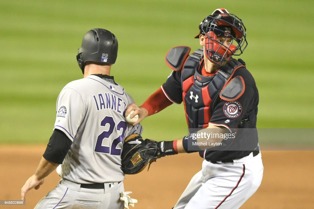 Matt Wieters #32 of the Washington Nationals tags out Chris Iannetta #22 of the Colorado Rockies who tried to score on Ian Desmond #20 (not pictured) ground ball in the fifth inning during a baseball game at Nationals Park on April 12, 2018 in Washington, DC.