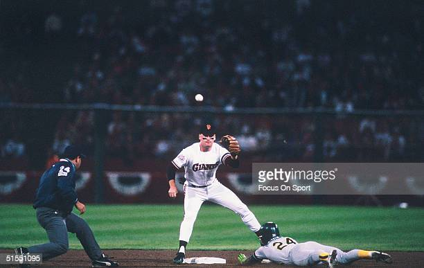 Matt Williams of the San Francisco Giants waits for a throw at second base as Rickey Henderson of the Oakland Athletics steals second base during the...