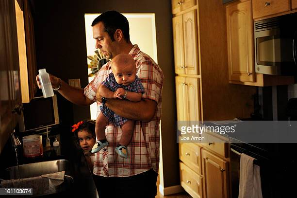 Matt Zarlengo mixing a bottle for his 3 month old baby Luciano as one of his 4 year old twins Ilaria watches in their Lakewood home Zarlengo has been...