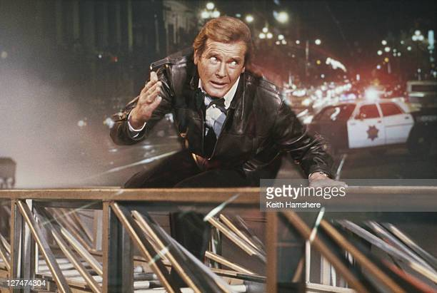 A matte shot of English actor Roger Moore as 007 clinging to a fire engine ladder in a publicity still for the James Bond film 'A View To A Kill'...