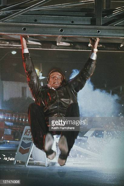 A matte shot of English actor Roger Moore as 007 hanging from a fire engine ladder in a publicity still for the James Bond film 'A View To A Kill'...