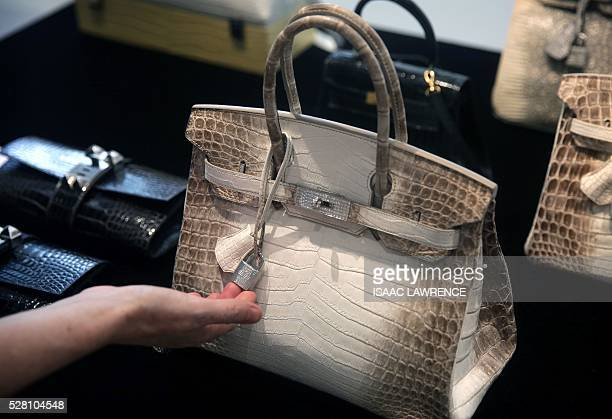 A Matte White Himalaya Niloticus Crocodile Diamond Birkin with 18K gold and diamond hardware one of the most valuable handbags in the world sits on...